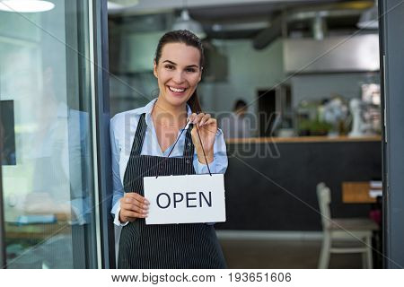Woman holding open sign in cafe