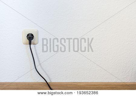 One Single European Plug On A White Wall