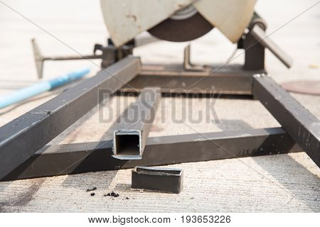 metal pipe cut placed near grinder machine.