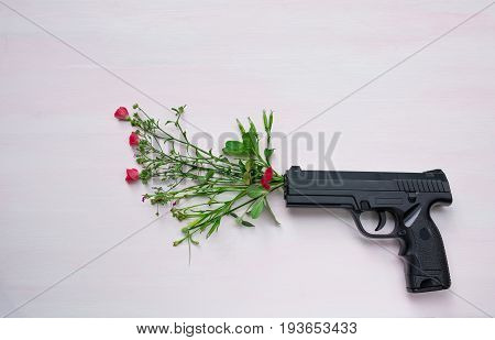 Handgun on wooden background with flowers.War and peace full with hand gun.
