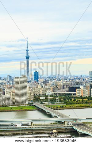 Tokyo Skytree and Tokyo city and highway across Arakawa river to the city in the cloudy day