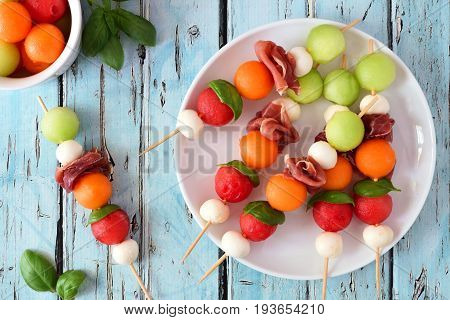 Plate Of Delicious Summer Fruit Skewers With Melon, Cheese And Prosciutto On A Rustic Blue Wood Back