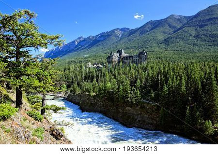 BANFF CANADA - JUNE 27 2017: View over Bow Falls to the Banff Springs Hotel. The castle-like luxury hotel was built in the late 1800s and is scenically located within the Canadian Rocky Mountains.