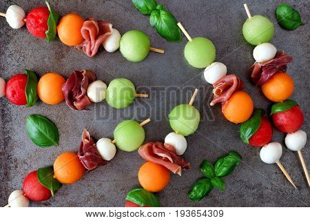 Colorful Summer Fruit Skewers With Melon, Cheese And Prosciutto, Overhead View On A Rustic Metallic
