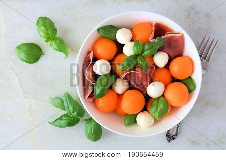 Summer Salad With Cantaloupe, Mozzarella, Prosciutto, And Basil, Above View On A White Marble Backgr