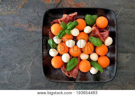 Colorful Salad With Cantaloupe, Mozzarella, Prosciutto And Basil, Top View On A Dark Slate Backgroun