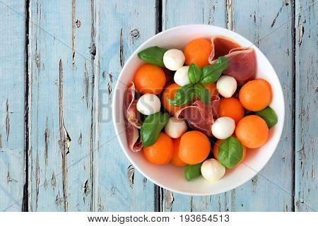 Salad With Cantaloupe, Mozzarella, Prosciutto And Basil, Above View On A Rustic Blue Wood Background