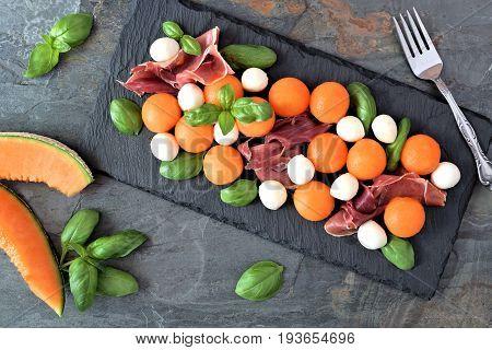Colorful Salad With Cantaloupe, Mozzarella, Prosciutto And Basil, Overhead View On A Slate Backgroun