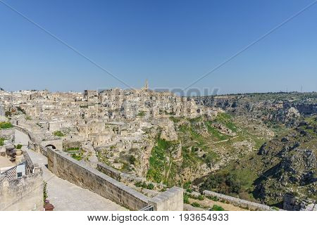 beautiful horizon view of ancient ghost town of Matera (Sassi di Matera) in beautiful bright sun shine with blue sky south Italy.