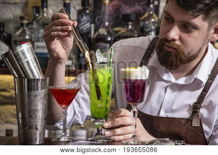 close up of bartender making alcohol coctail in restaurant