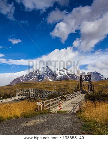 The famous Torres rocks. Wooden narrow bridge through a small stream. Mountains  in Torres del Paine National Park, Chile. The concept of active and extreme tourism