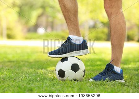 Legs of young man with soccer ball in green park on sunny day