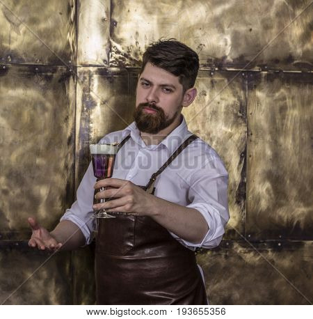 Portrait of brutal  bartender standing and smiling in bar and holding cocktail in a hand