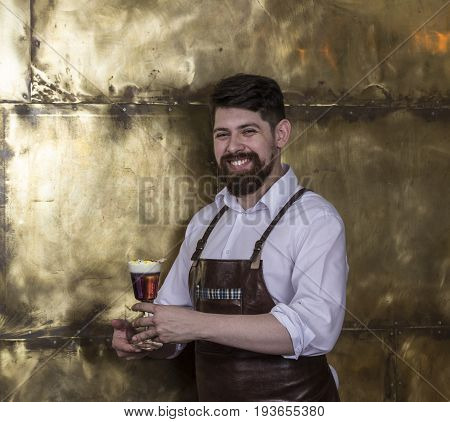 Portrait of cheerful  bartender standing and smiling in bar and holding cocktail in a hand