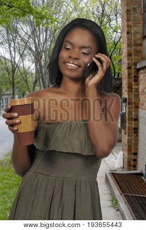 Black African American woman using a cell phone will holding coffee