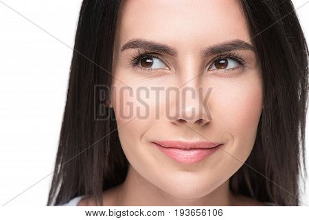 Dreamful beautiful young woman is smiling gently. She is looking sideways with aspiration. Close up of her face