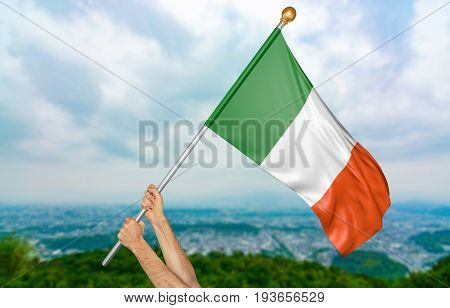Young man's hands proudly waving the Ireland national flag in the sky, part 3D rendering