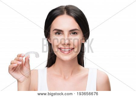 I take care of my teeth. Portrait of happy brunette girl showing silicone clear aligner. She is standing and laughing. Isolated