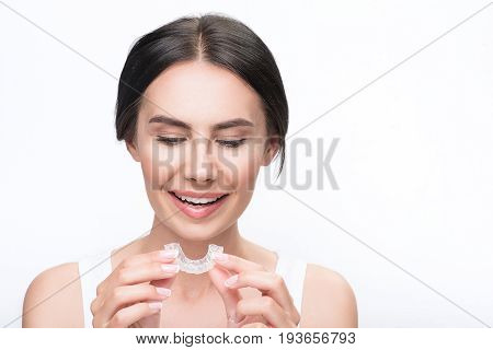 Portrait of excited young woman holding clear aligner and looking at it with interest. She is standing and smiling. Isolated