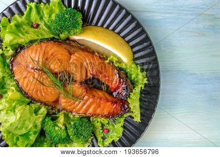 A closeup of a grilled salmon steak, with fresh green salad, broccoli sprouts, a slice of lemon, and pink peppercorns, on a teal background with a place for text