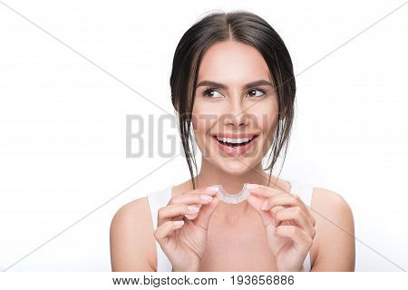 Ready to improve my bite. Portrait of happy young woman holding clear aligner near her mouth. She is looking aside with curiosity and smiling. Isolated and copy space