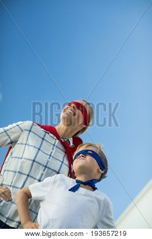 Smiling mother and son pretending to be superhero in garden