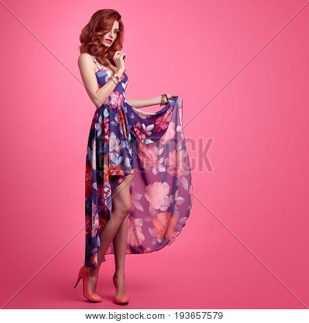 Fashion Sensual Sexy Redhead Model in fashion pose. Beauty Woman in Summer Outfit. Trendy Floral Dress, Stylish Curly Wavy hairstyle, Luxury fashion Heels. Playful Happy Romantic summer Lady on Pink