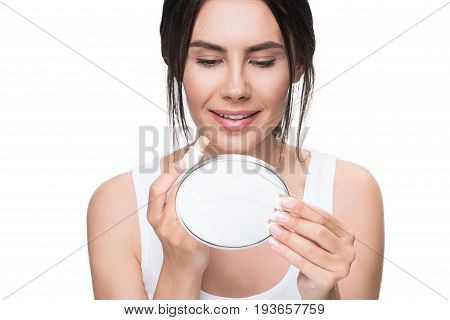 I like this color of my lips. Portrait of happy young woman applying lip gloss while looking at mirror with bright smile. Isolated
