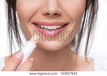 Close up of voluptuous female lips with lip gloss. Glad young woman is smiling while holding hygienic lipstick