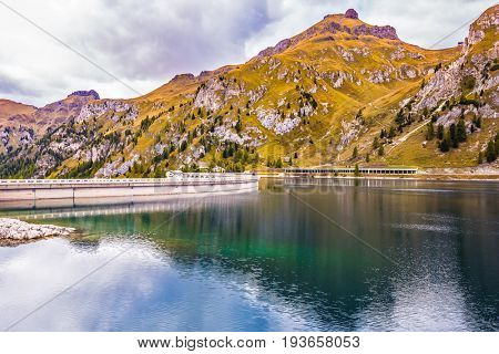 Magnificent glacial lake Lago di Fedaia in the Dolomites. Cloudy cold autumn day. Powerful dam blocked the lake. The concept of ecological and extreme tourism