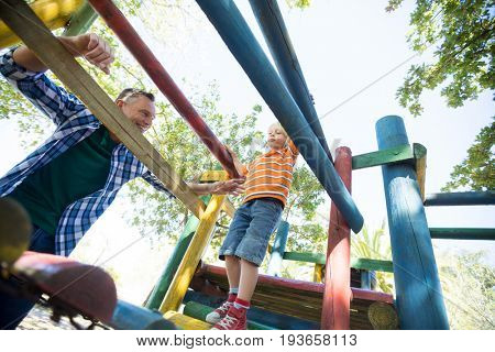 Low angle view of father looking at son walking on jungle gym at playground