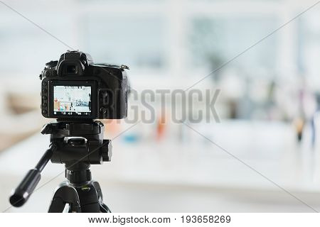 Close up focus on video camera shooting someone blog about cosmetic products. Copy space in right side