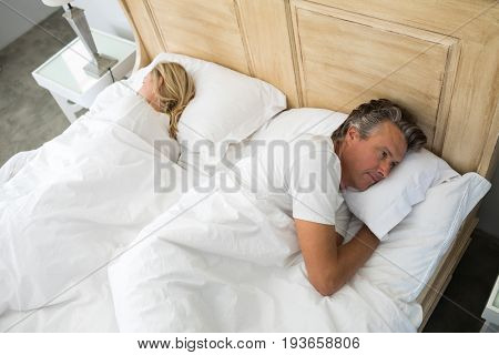 Couple lying on bed after having an argument in bedroom