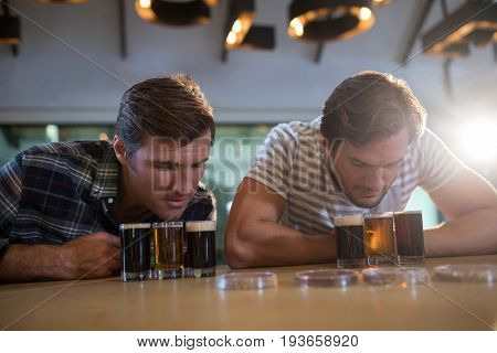 Male friends looking at beer glass while sitting at bar counter