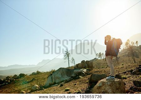Young man in hiking gear standing on a rock shielding his eyes from the sun and admiring the view while out for a hike
