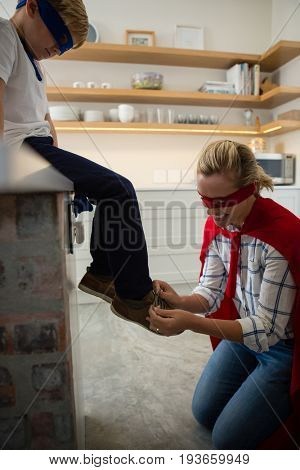 Mother with son in superhero costume tying his shoelaces at home