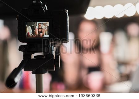 Close up focus on camera screen recording young female blogger advertising facial cream. She is sitting at table in dressing room and laughing