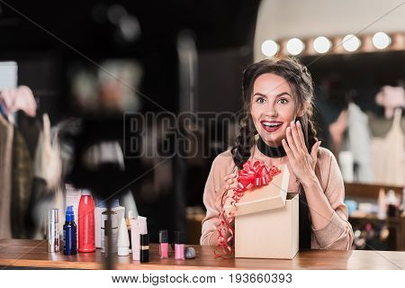 What a wonderful present. Portrait of glad girl opening box and looking at camera with admiration. She is sitting at desk near cosmetic items in dressing room