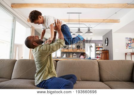 Father And Son Playing On Sofa In Lounge Together