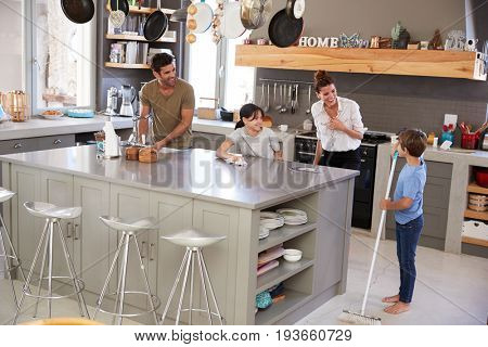 Children Helping Parents With Domestic Chores In Kitchen