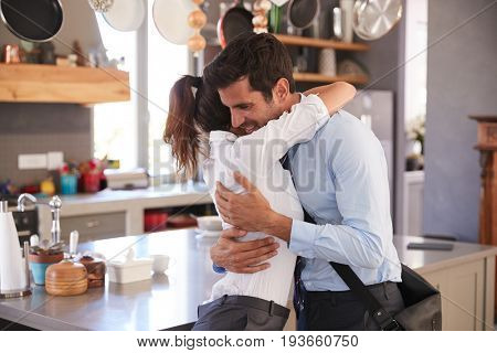 Husband Saying Goodbye To Wife As He Leaves For Work