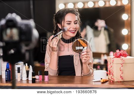 Perfect make-up. Portrait of beautiful brunette girl applying powder on her face while sitting backstage. She is holding mirror with satisfaction and recording video for blog