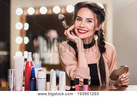 Portrait of pretty girl with perfect make-up. She is sitting at desk near cosmetic items backstage and smiling