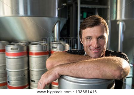 Close up portrait of smiling worker leaning on kegs at warehouse