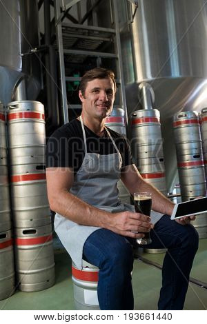 Portrait of smiling worker holding tablet and beer while sitting by kegs at warehouse