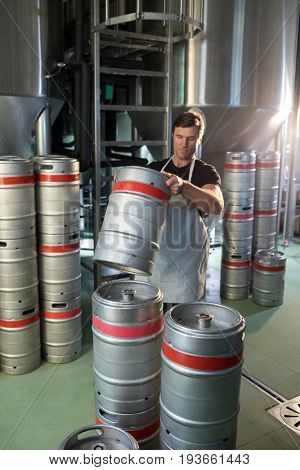 Male worker arranging kegs at warehouse