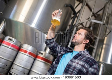 Low angle view of man examining beer in beaker at factory