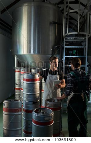 Workers talking while standing by kegs at warehouse