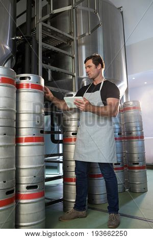 Full length of worker holding digital tablet counting kegs at warehouse