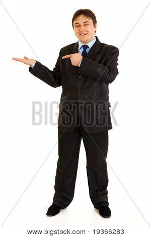 Full length portrait of smiling modern businessman pointing finger on empty hand isolated on white